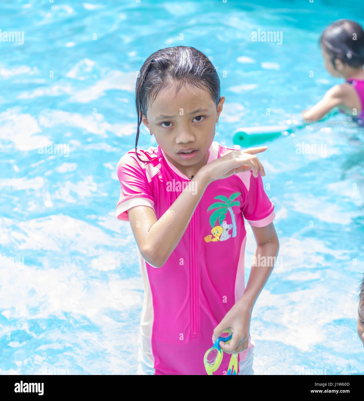 Portrait de jeune fille asiatique coupable (Kid) à la piscine Photo Stock
