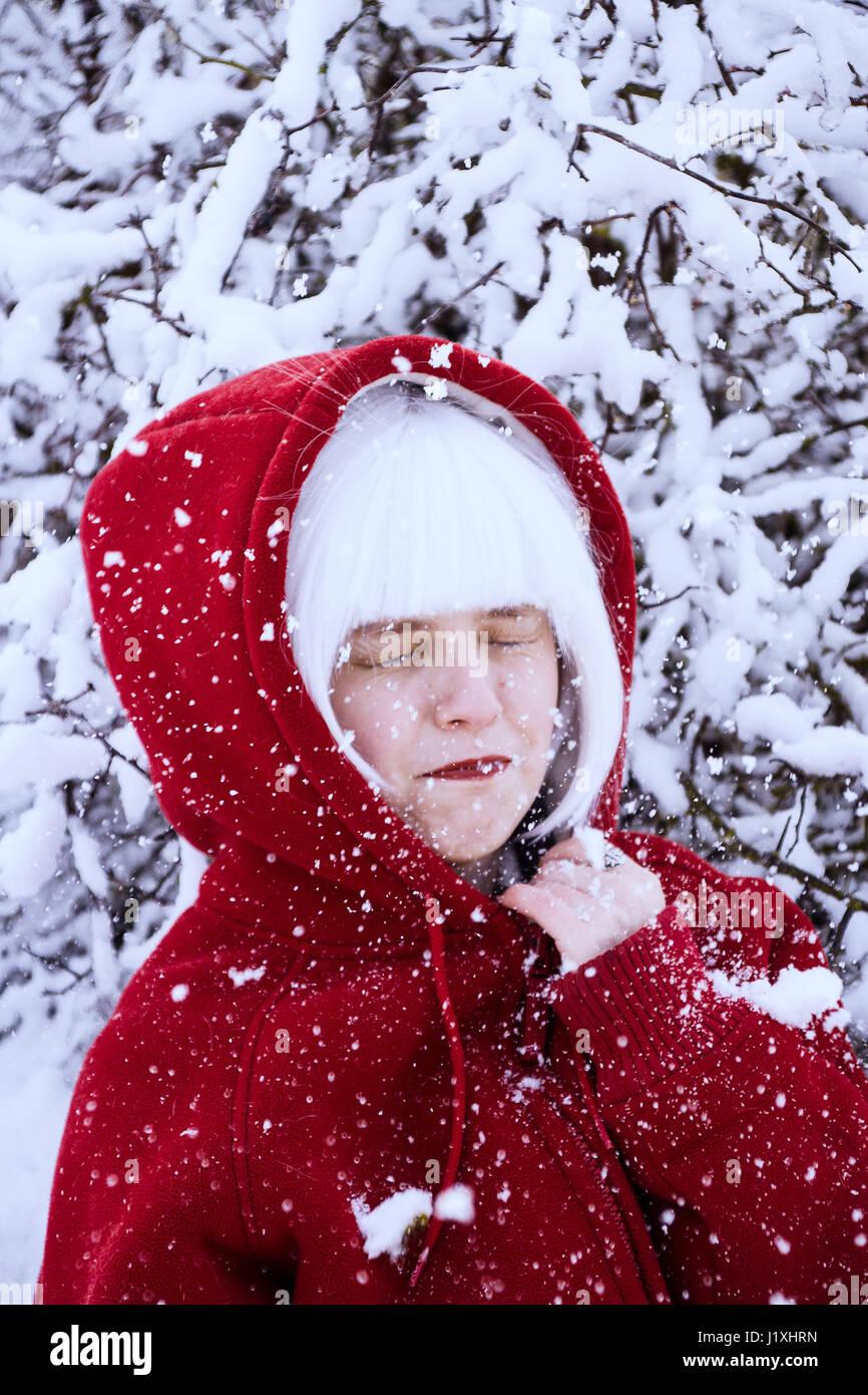 Jeune femme avec capuche rouge et cheveux blancs en hiver Photo Stock