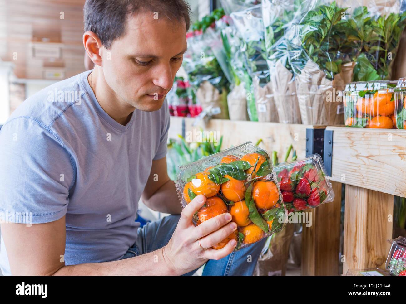 Jeune homme tenant les boîtes en plastique avec cueillette de mandarines en magasin Photo Stock
