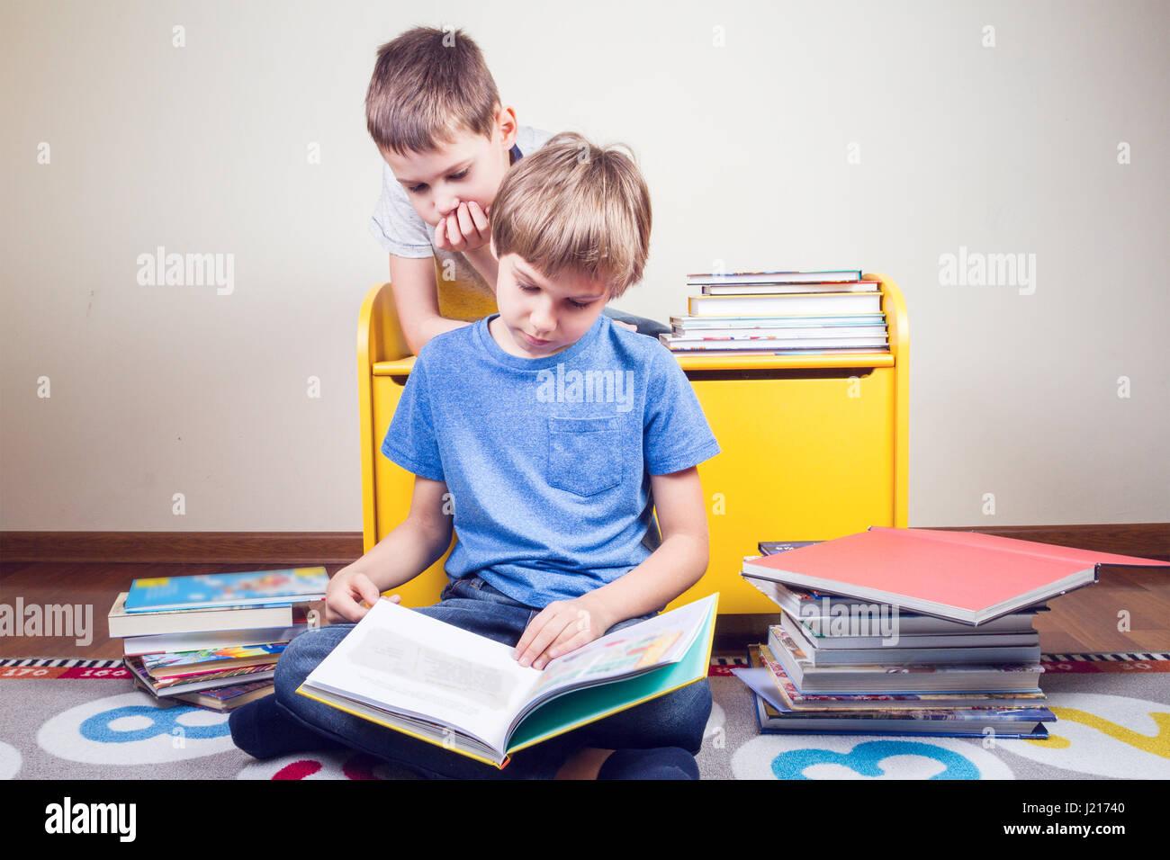La lecture d'un livre pour enfants. Garçon lit une histoire à son frère à la  maison