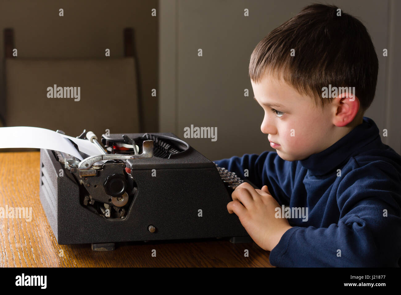 Cute little boy en tapant une lettre sur un noir vintage typewriter à la maison. À l'ennui, concentré Photo Stock