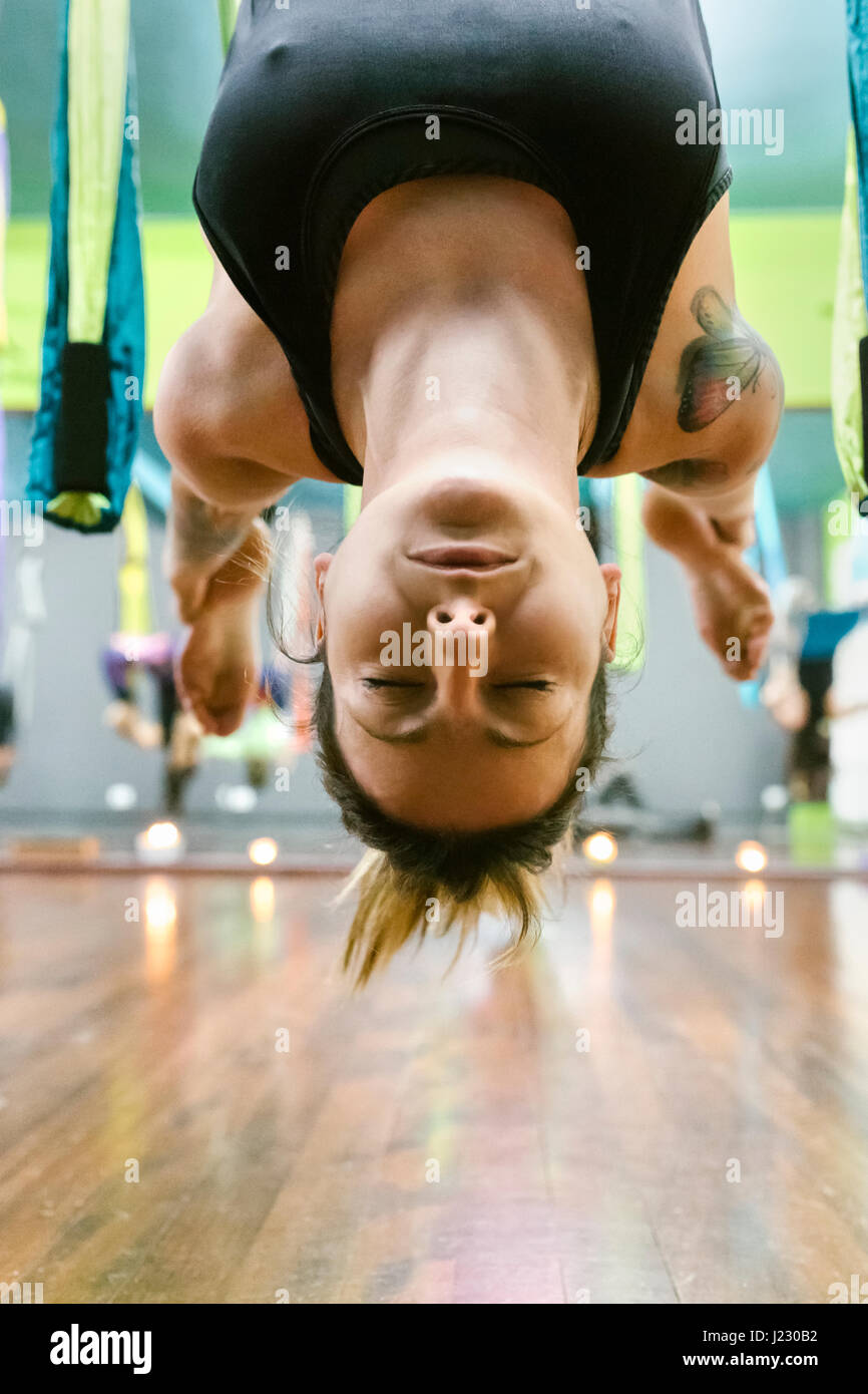 Woman practicing yoga aérien en classe Photo Stock