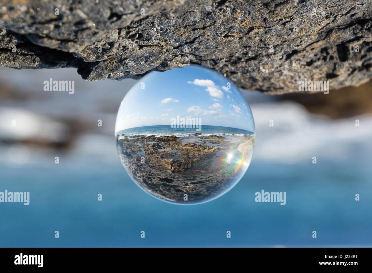 Paysage de mer et rochers vus à travers une bille de verre Photo Stock