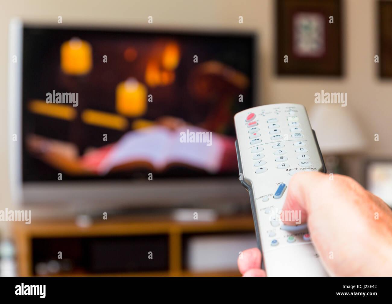 Personne à regarder la télévision et de changer de chaîne en utilisant la télécommande Photo Stock