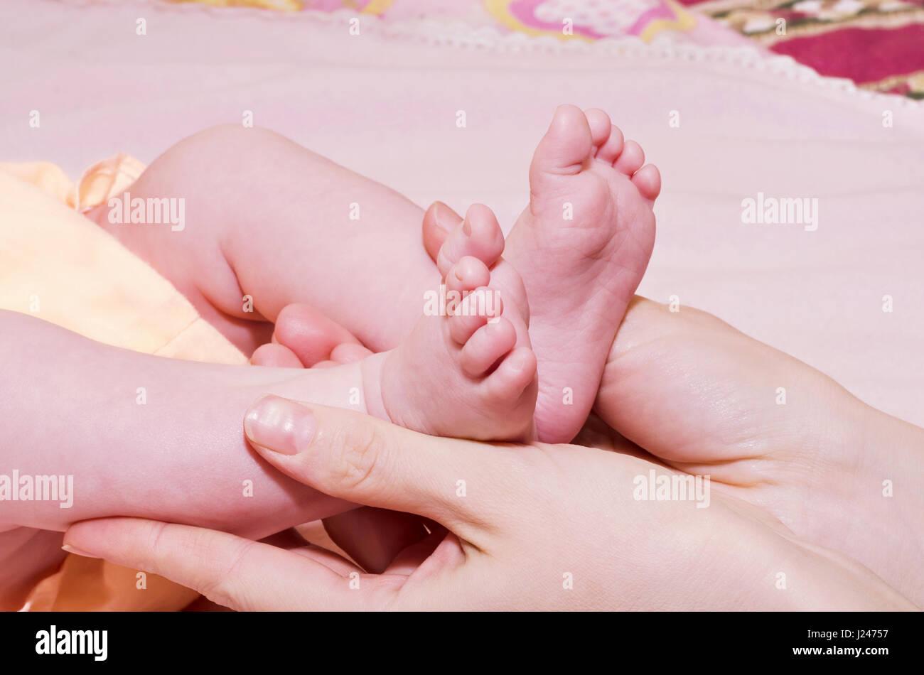 Les petits pieds dans les mains des mamans Photo Stock
