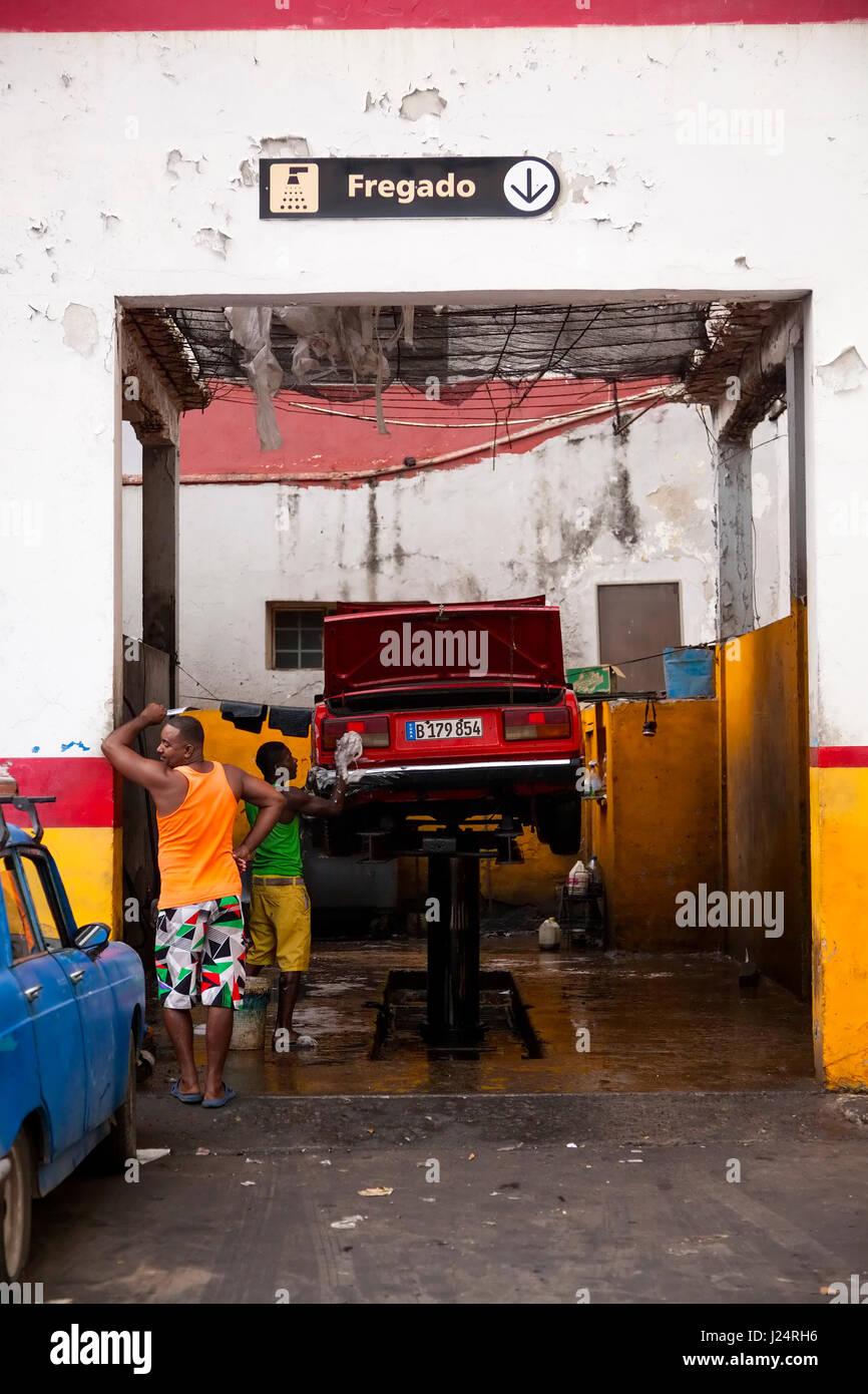 Un homme lave une voiture à l'intérieur d'un garage automobile à La Havane, Cuba. Photo Stock