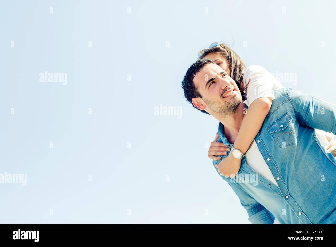 Playful couple profitant de leurs vacances d'été que l'homme porte la woman piggyback Photo Stock
