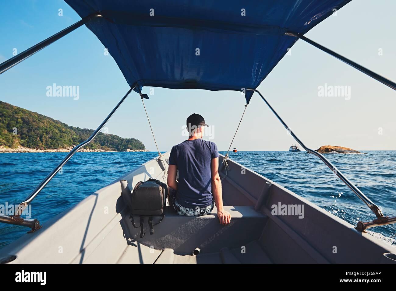 Aventure sur la mer. Jeune homme voyageant par bateau à moteur. Photo Stock