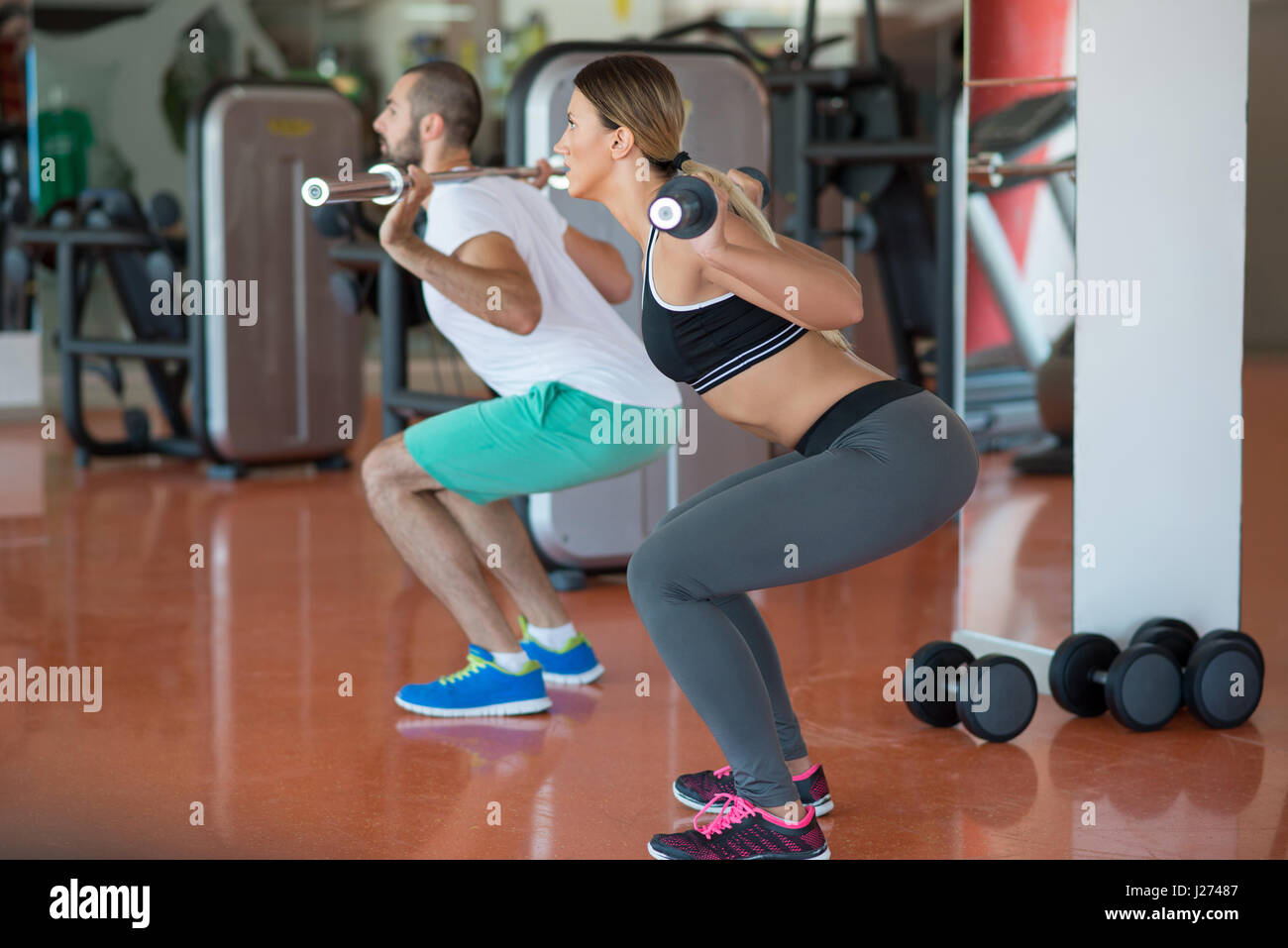 Young man and woman flexing muscles de l'épaule et appuyez sur squat in gym Photo Stock