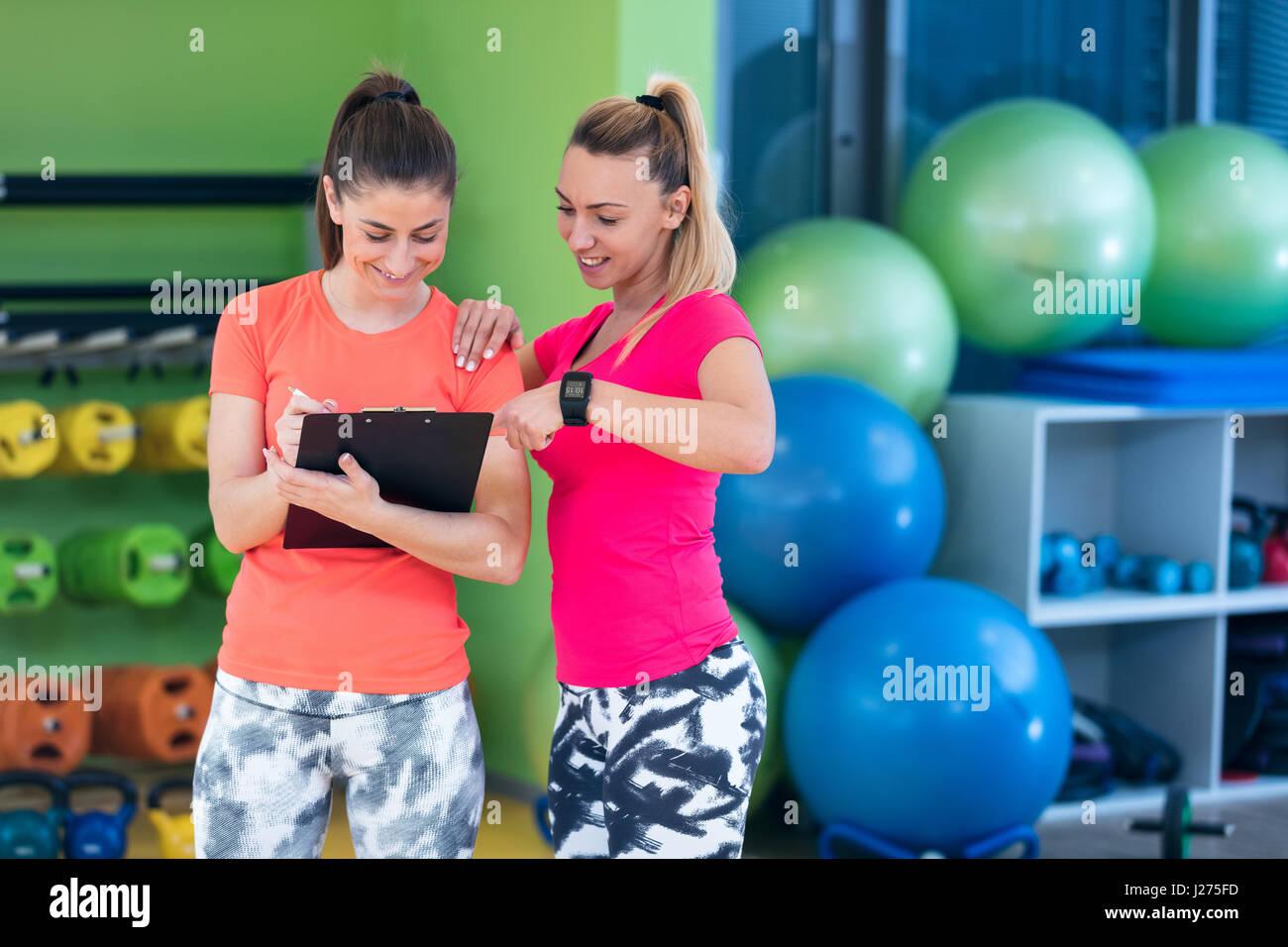 Deux jeunes femme jouissant de sa routine d'exercice dans la salle de sport de rire et sourire Photo Stock