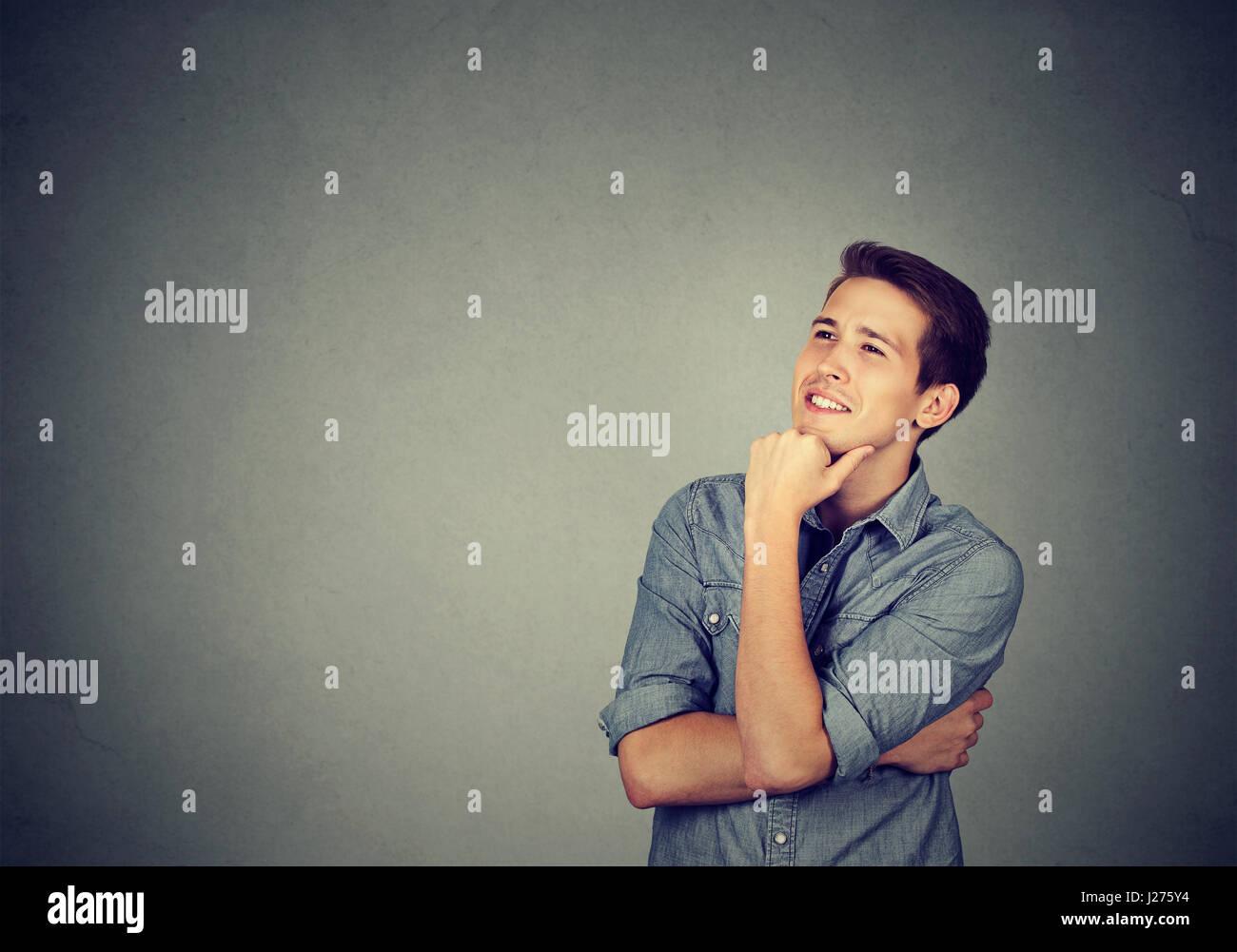 Heureux jeune homme jusqu'à la rêverie pensée isolé sur fond de mur gris Photo Stock