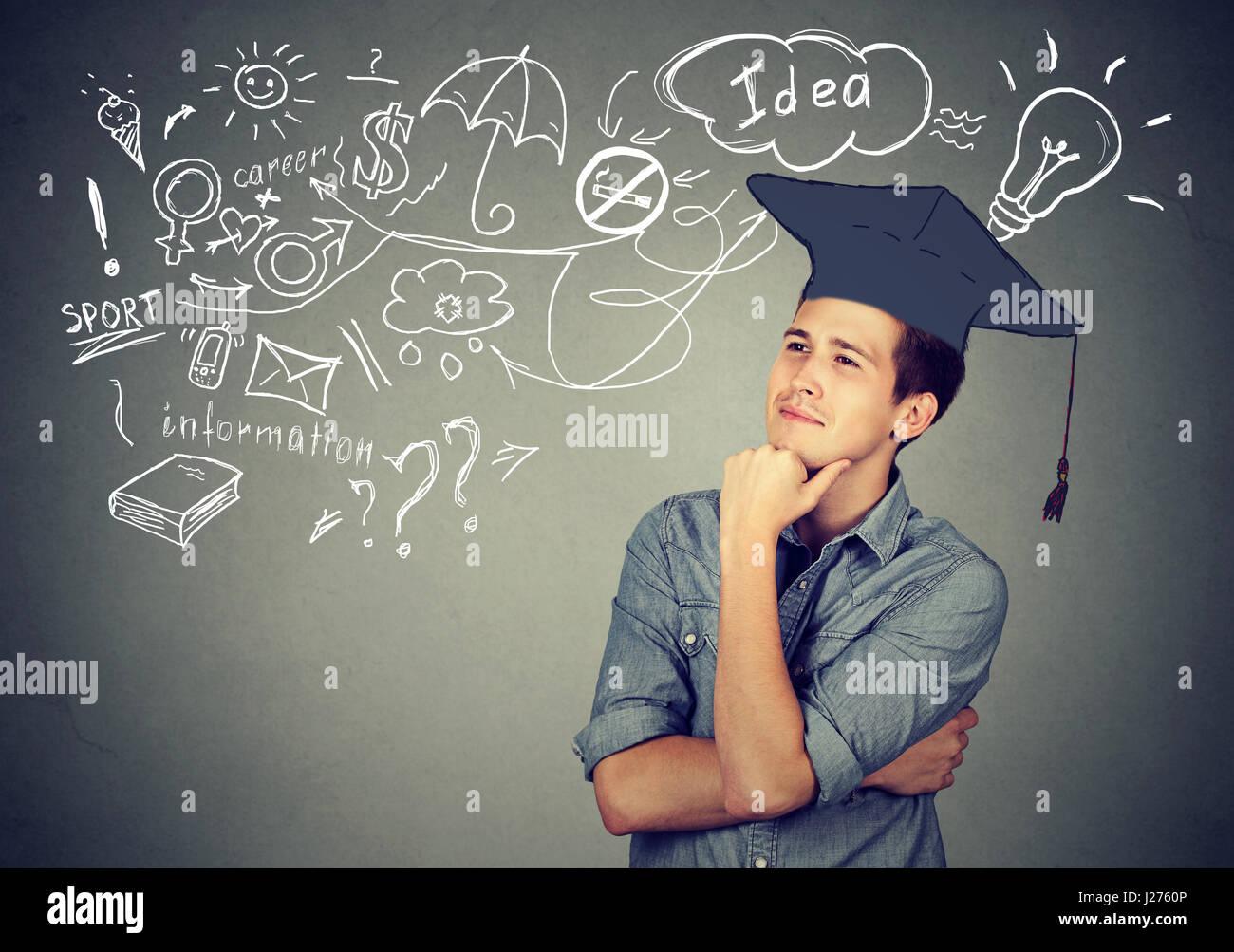 Jeune homme séduisant avec graduation hat jusqu'à la réflexion sur l'éducation a beaucoup Photo Stock
