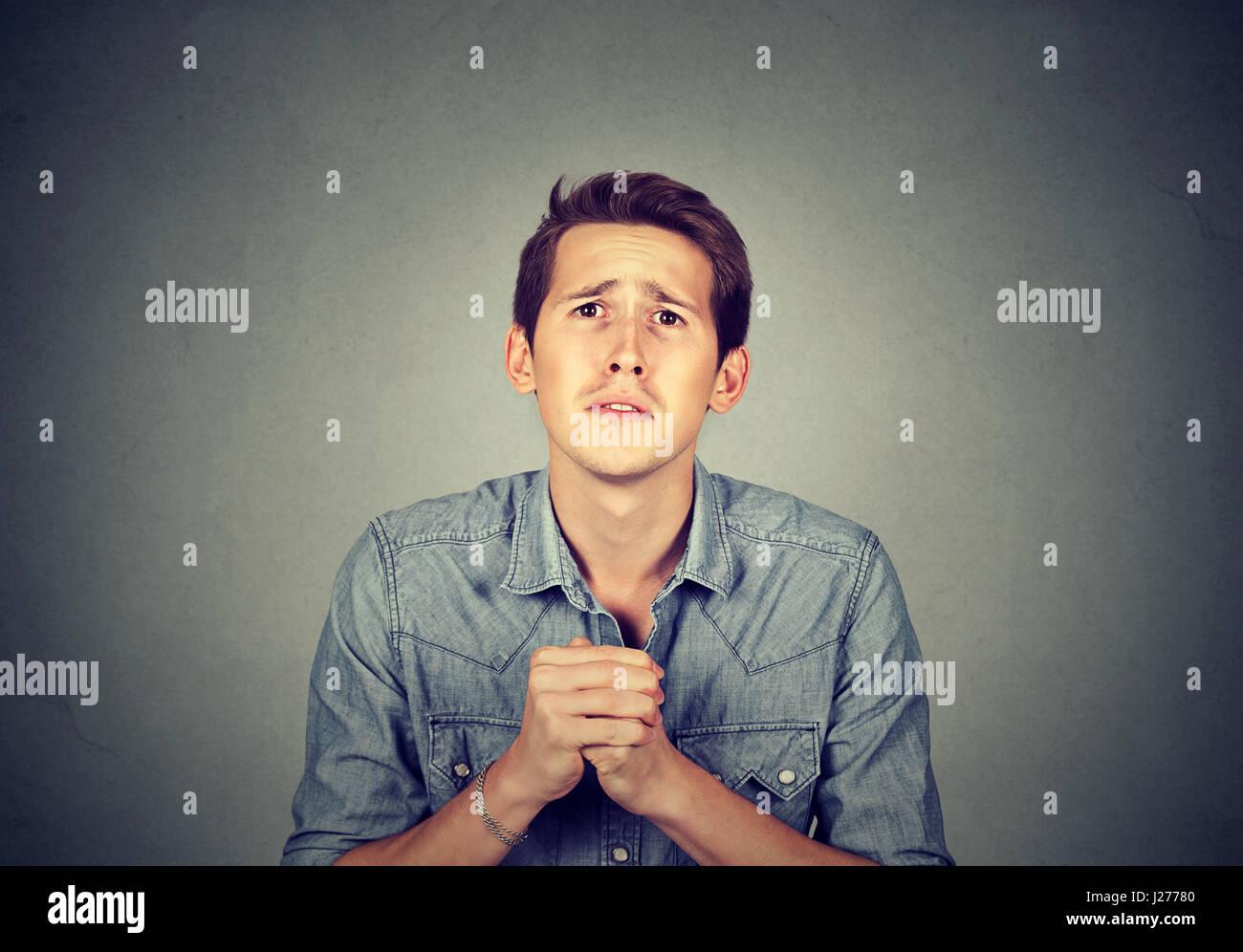 Jeune homme désespéré montrant les mains jointes, veuillez plutôt désolé pour l'erreur Photo Stock