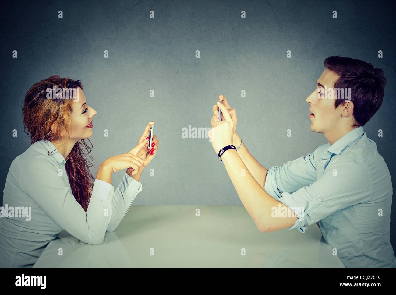 Jeune homme et femme assis à table à l'aide de téléphones mobiles, sms via les réseaux Photo Stock