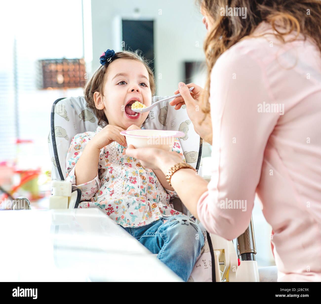 Mère nourrit sa fille bien-aimée Photo Stock