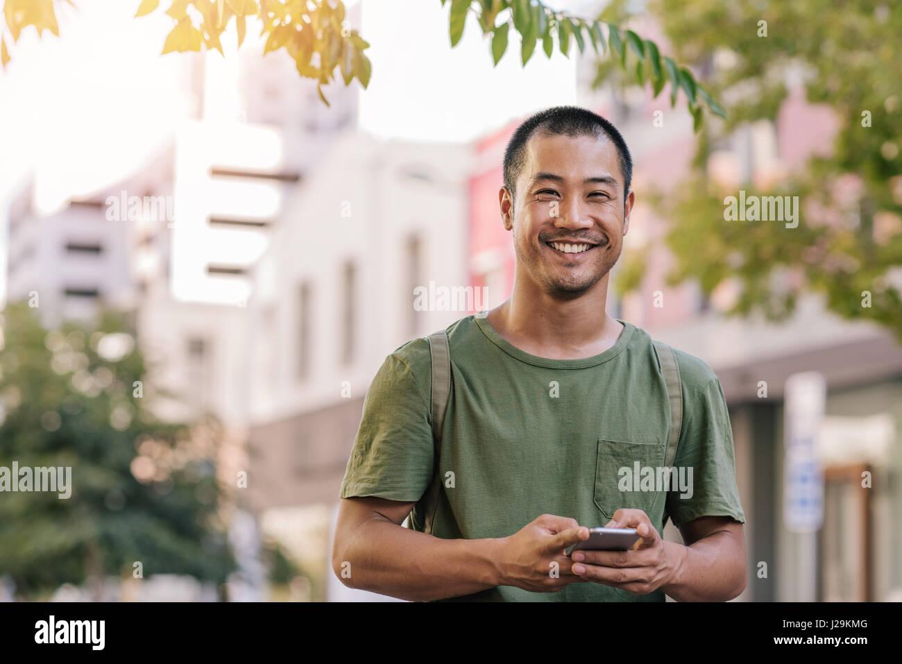 Young Asian man de l'envoi d'un texte sur son cellulaire à l'extérieur Photo Stock