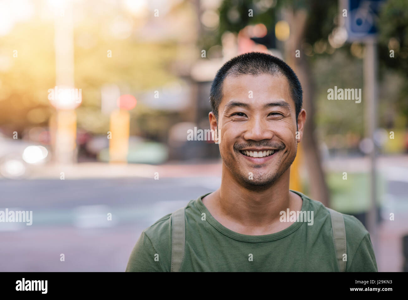 Young Asian man smiling avec confiance sur une rue de la ville Photo Stock