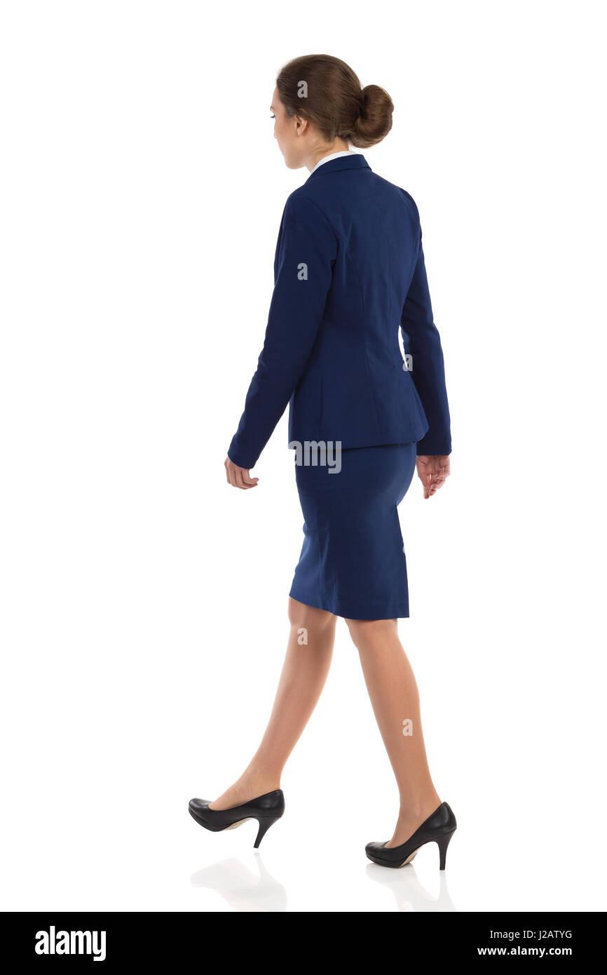 Jeune femme en costume bleu, jupe et talons hauts noir marche à pied. Vue latérale arrière. Studio Photo Stock