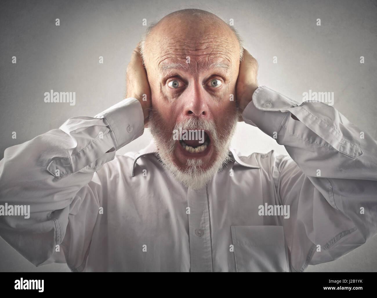 Peur vieil homme couvrant ses oreilles Banque D'Images