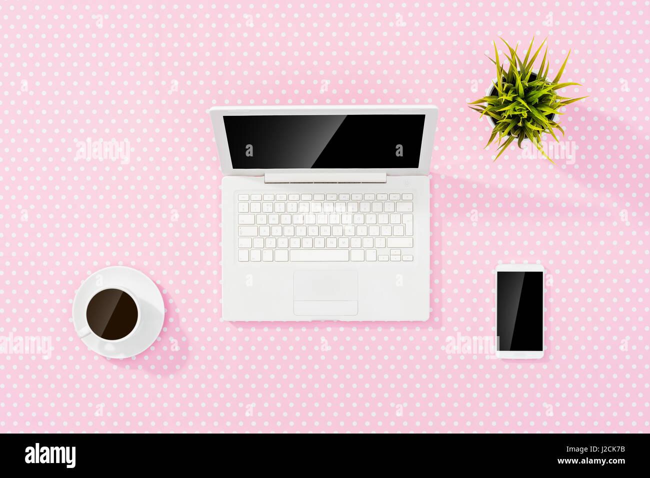 Bureau rose bureau avec ordinateur portable blanc smart phone et