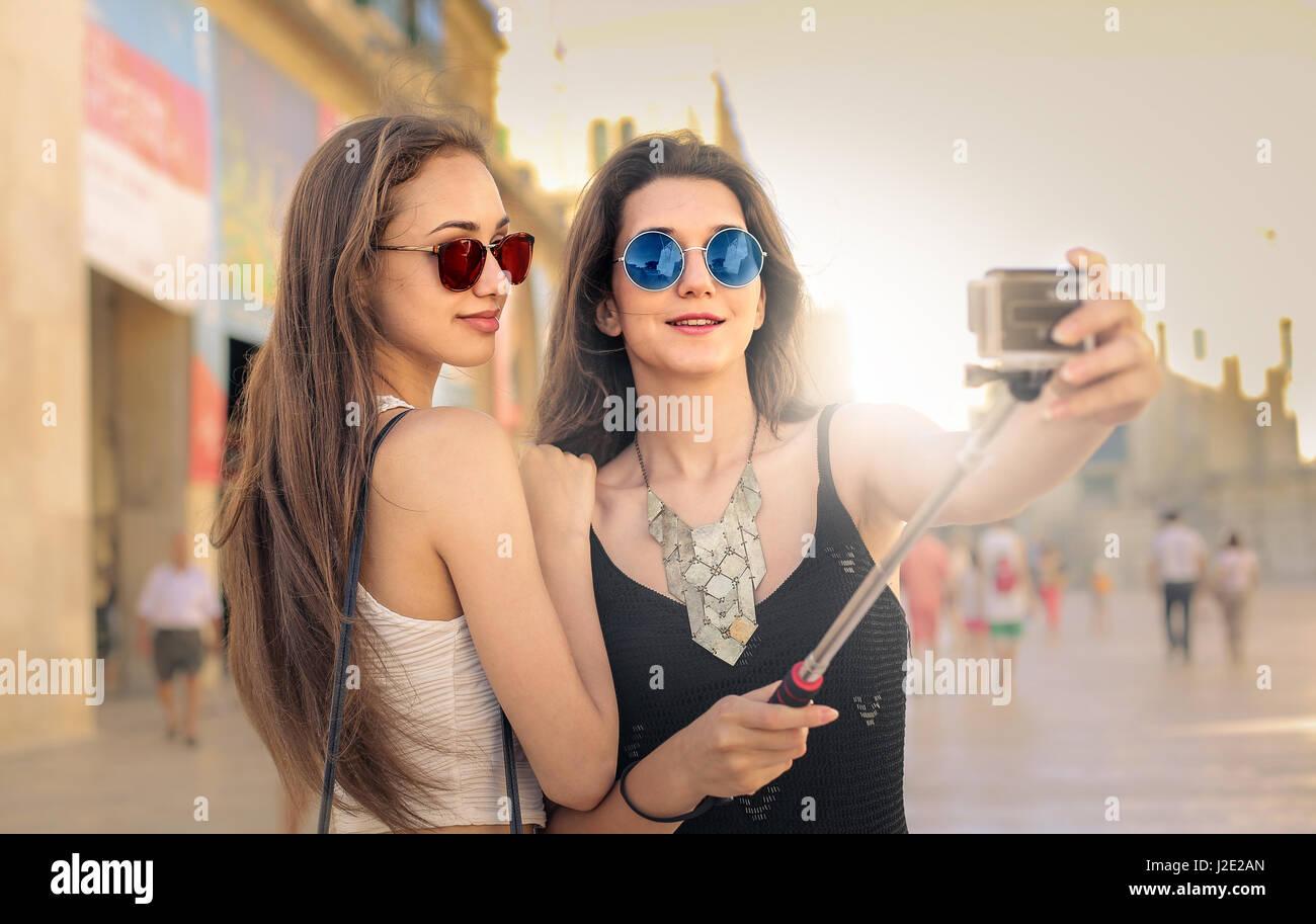 2 jeunes femmes dans la ville en prenant un selfies Photo Stock