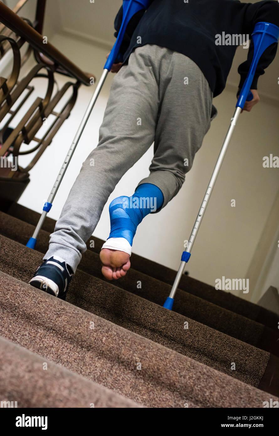 un jeune adulte avec des béquilles et son pied bandé dans le plâtre