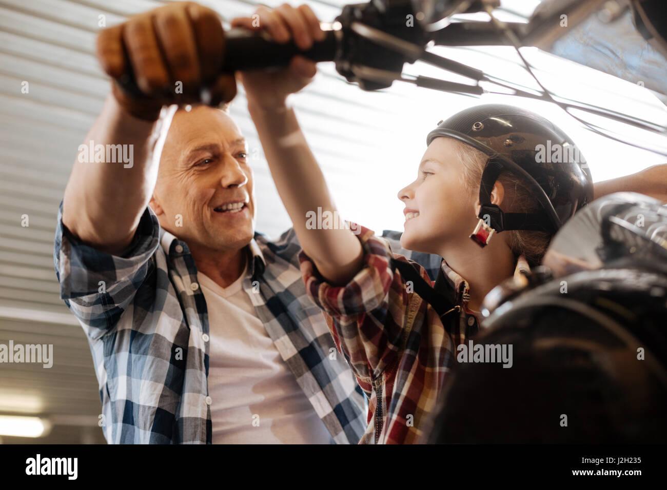 Famille inventive sincère de leur temps en garage Photo Stock