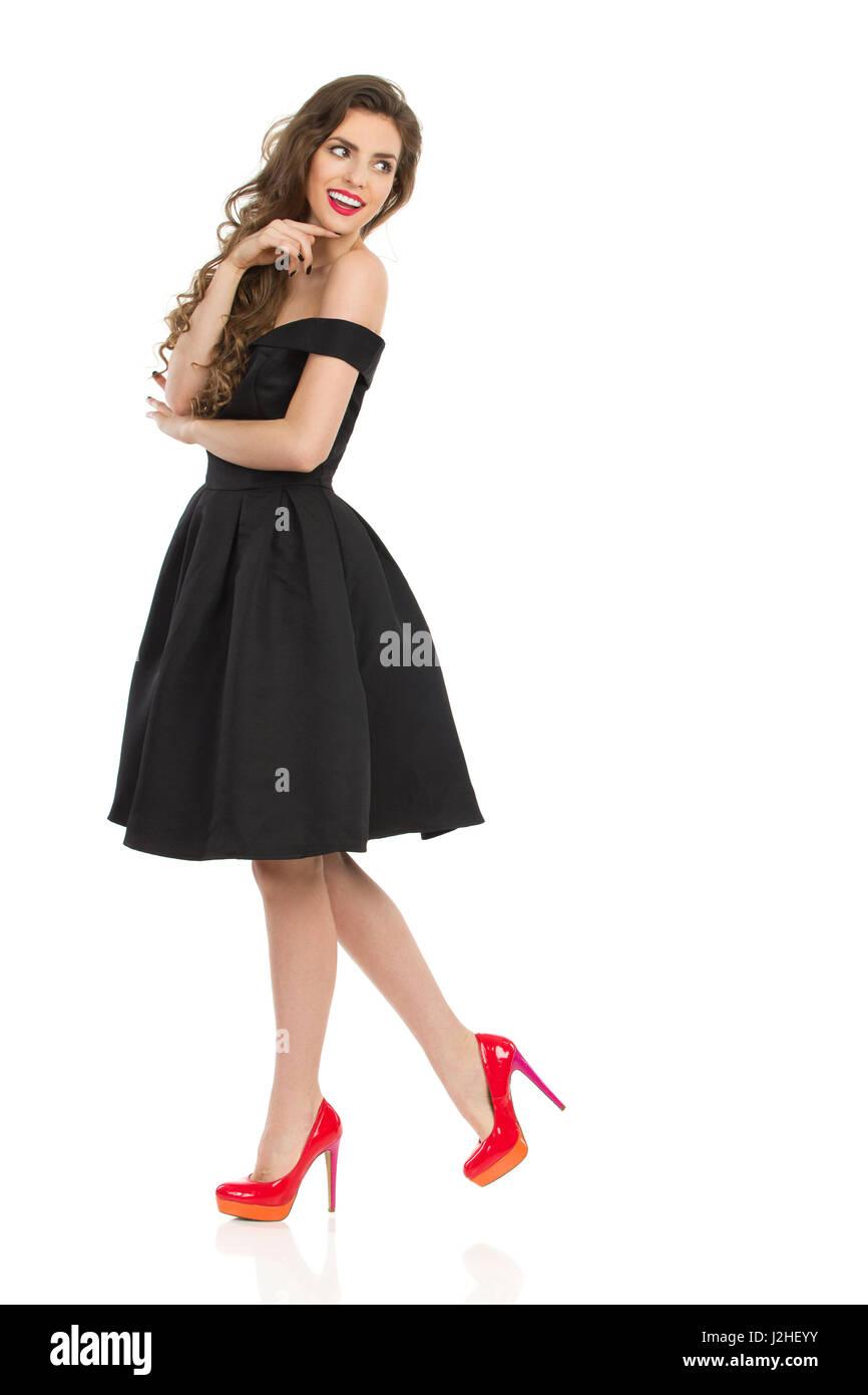 91e1de5758f Belle jeune femme élégante en robe de cocktail noire et rouge hauts talons  tient la main