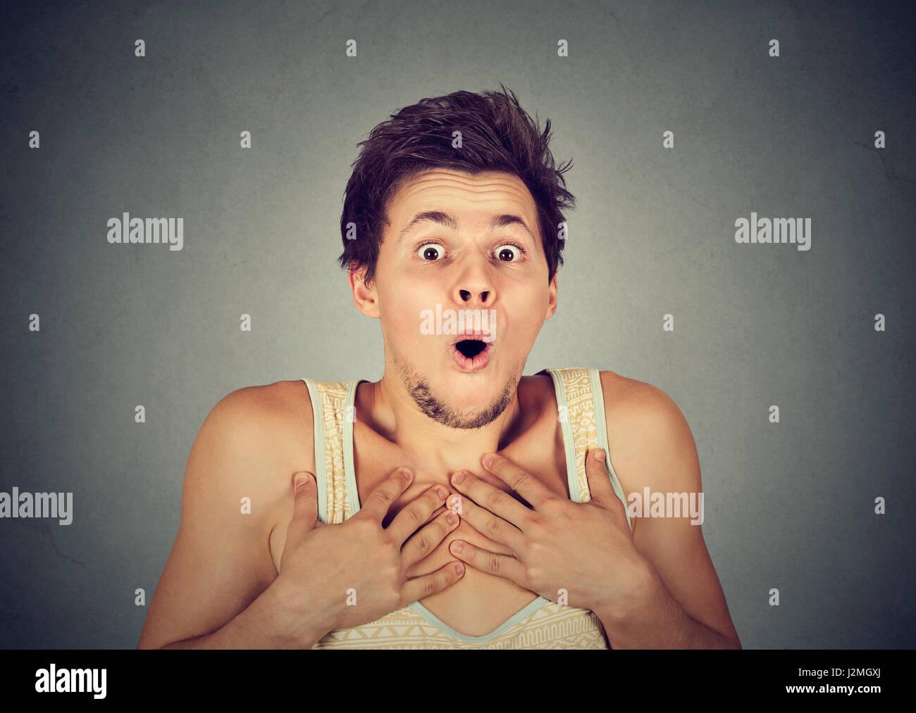 Jeune homme choqué surpris en pleine d'incrédulité avec les mains sur la poitrine Photo Stock