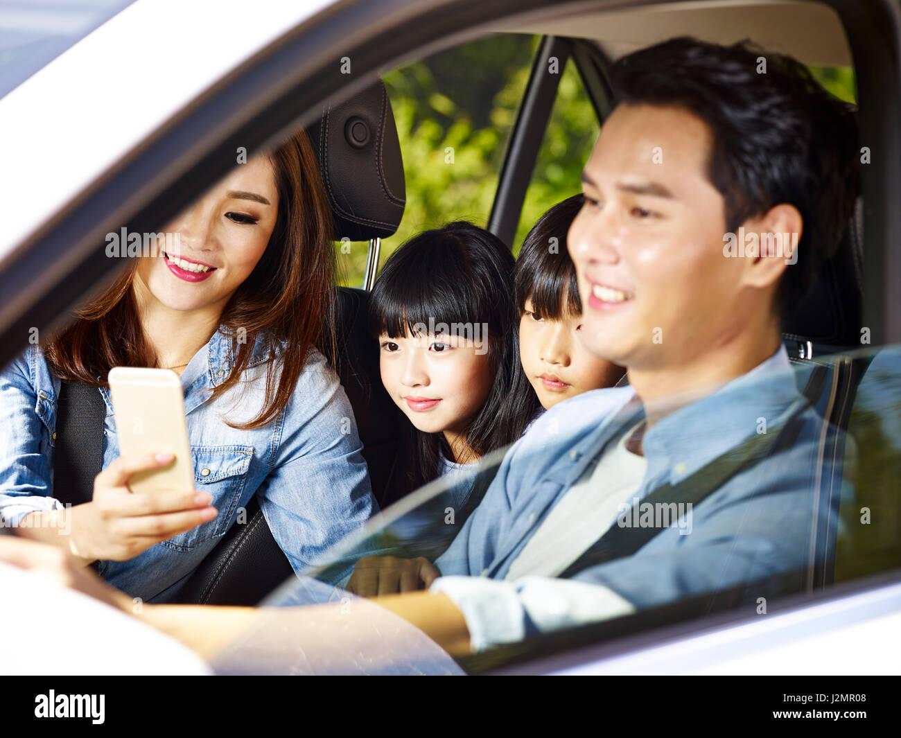 Happy asian famille avec deux enfants qui voyagent en voiture, tandis que le père de la mère à l'aide Photo Stock