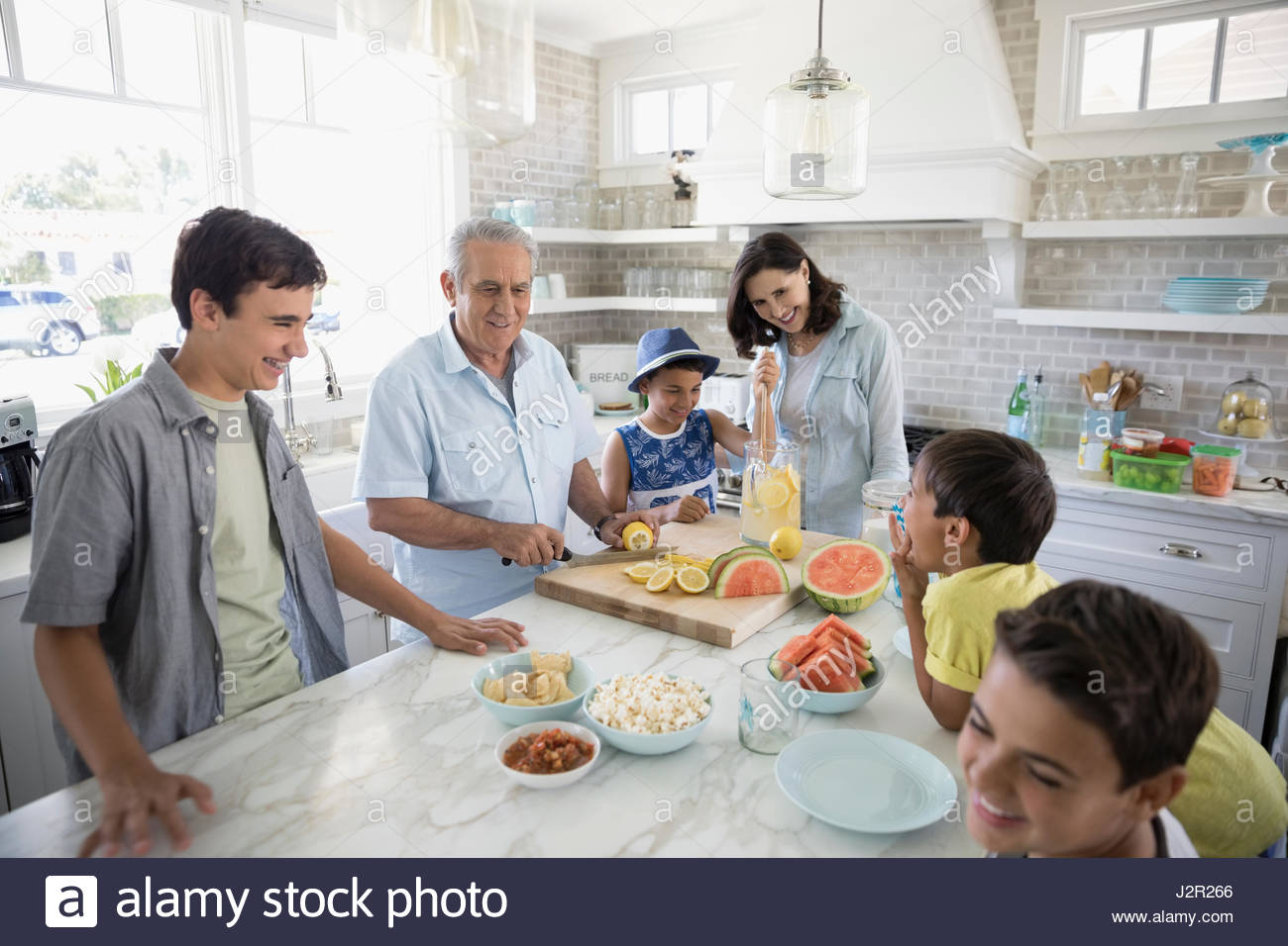 Multi-generation family making lemonade et grignoter dans la cuisine Photo Stock