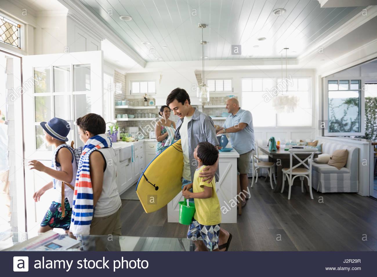Famille avec le body-board et serviette de plage laissant beach house Photo Stock