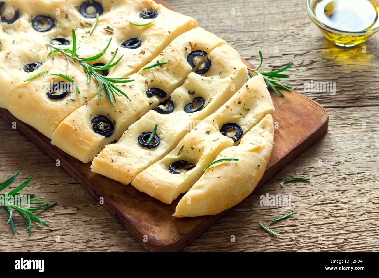 Focaccia italienne traditionnelle, aux olives noires et romarin - focaccia pain plat fait maison Photo Stock