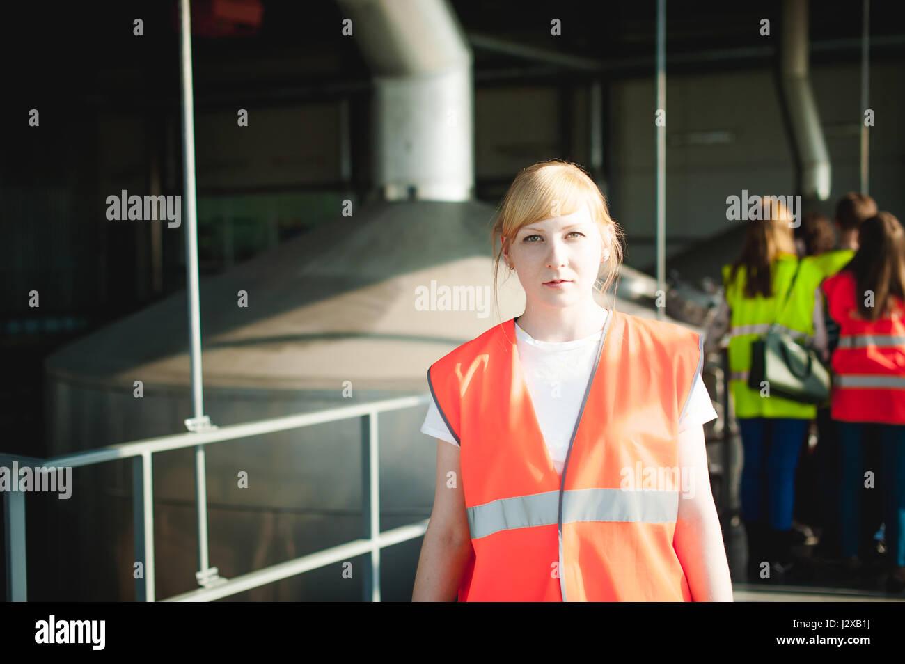 Femme blonde en salopette, sur la visite de la brasserie plante dans les locaux industriels, au milieu d'une foule de gens dans les gilets pare-balles, d'inspecter une usine pour la formation p Banque D'Images