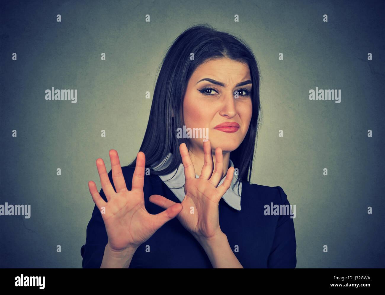 Jeune femme avec expression dégoûtée en esquivant quelque chose Photo Stock