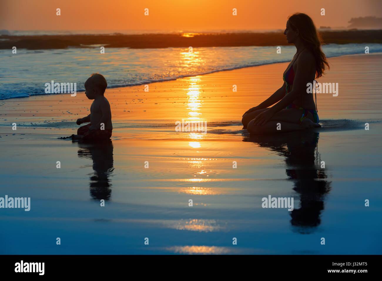 Piscine de la famille fun sur plage de sable noir avec vue mer surf. Happy mother, baby son s'asseoir et regarder Photo Stock