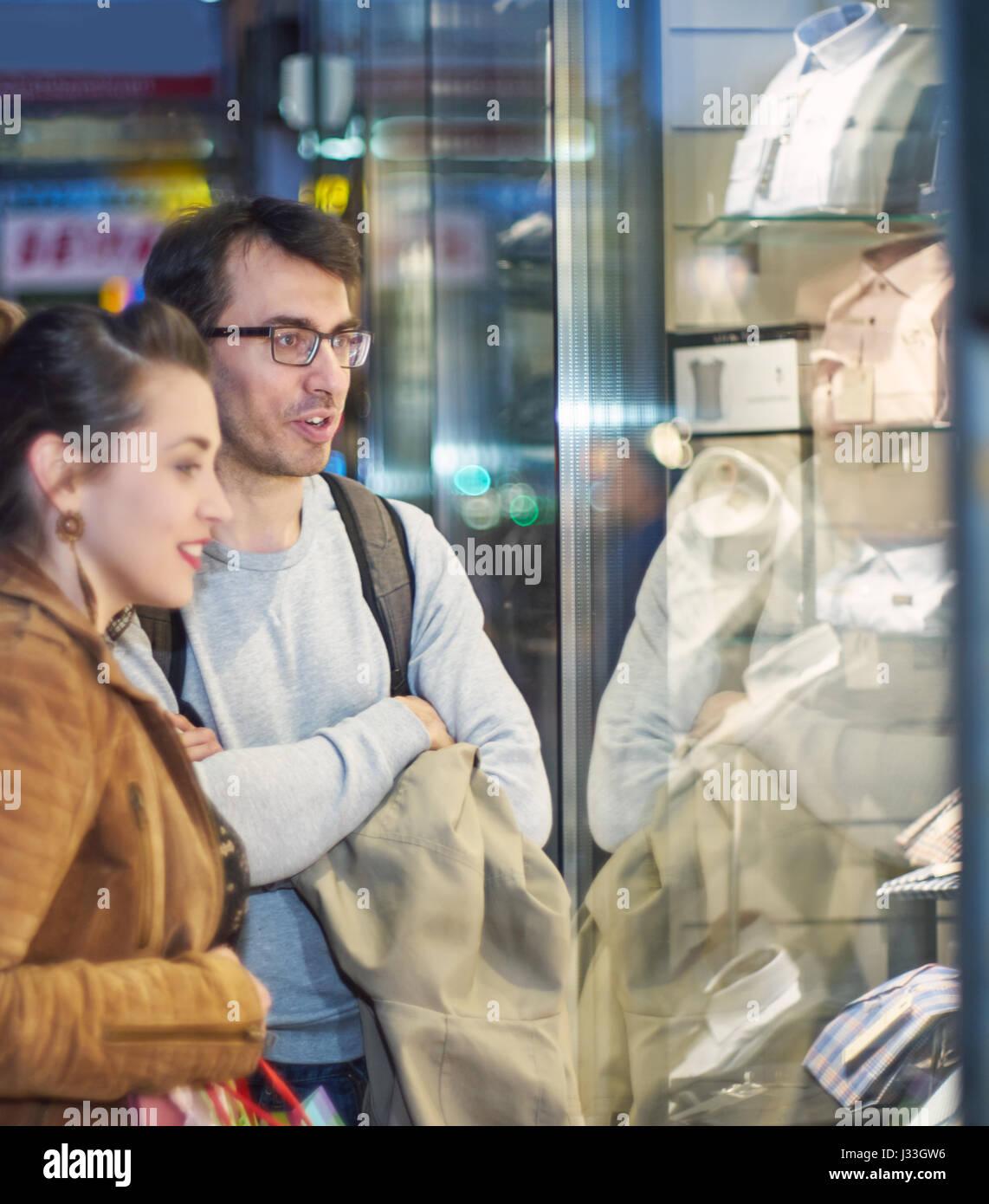 La femme et l'homme en face d'une boutique de vêtements Photo Stock