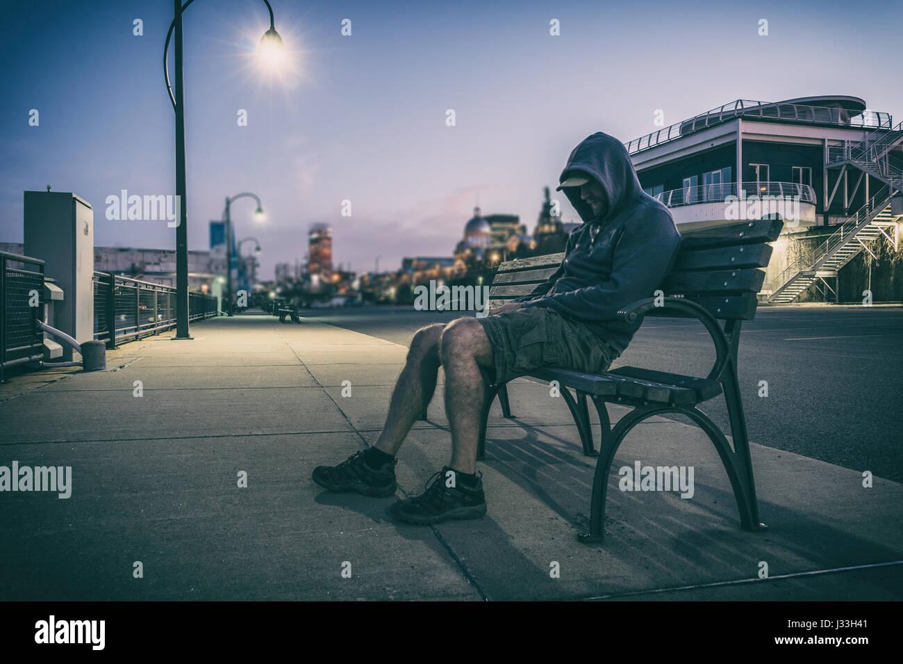 L'homme triste et solitaire avec face cachée assise sur un banc au coucher du soleil Photo Stock