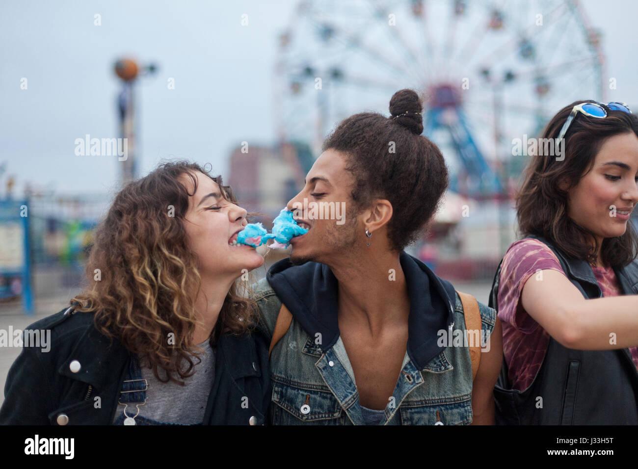 Friends eating Cotton Candy dans un parc d'attractions Banque D'Images