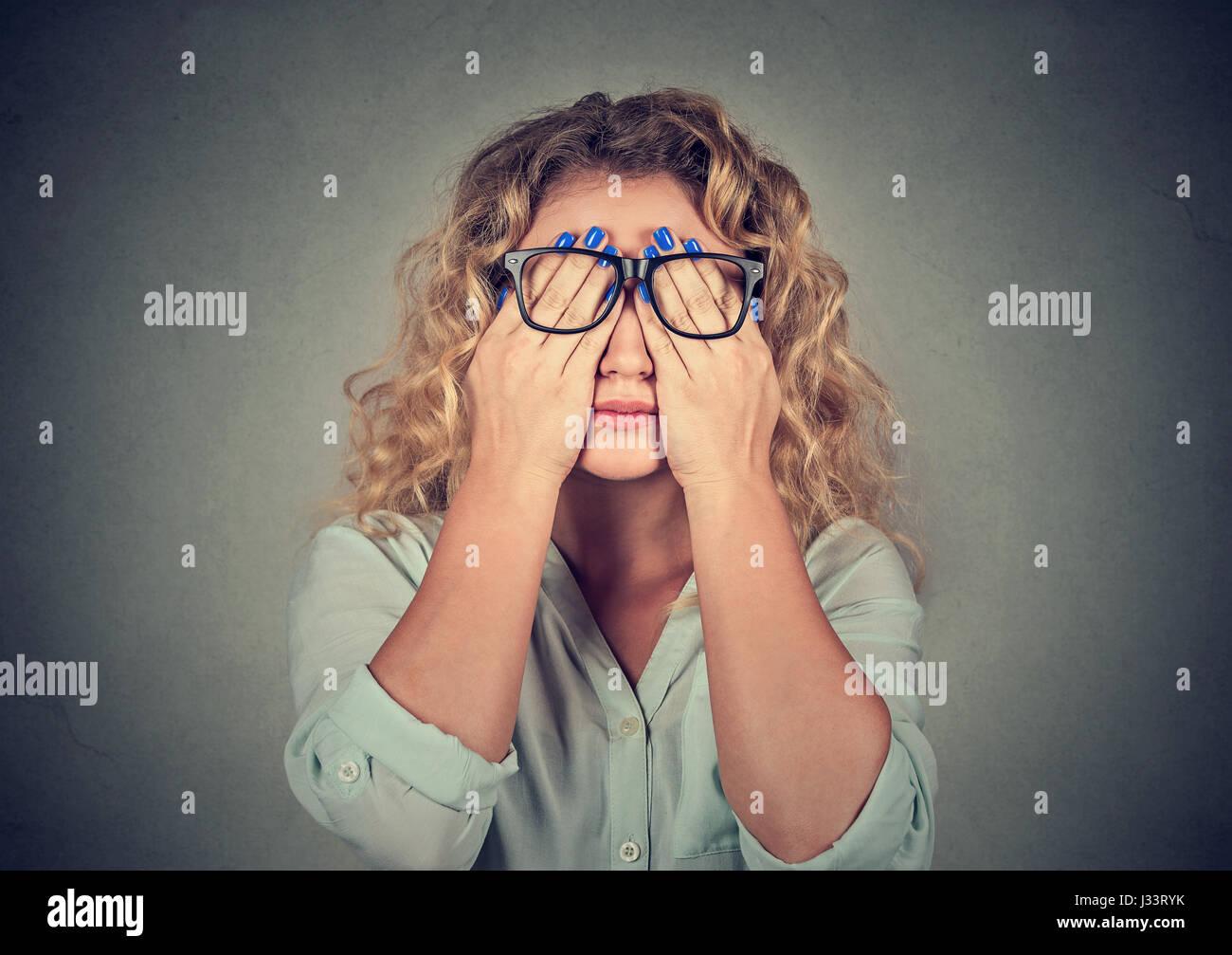 Closeup portrait jeune femme dans les verres couvrant visage yeux à l'aide de ses deux mains isolé Photo Stock