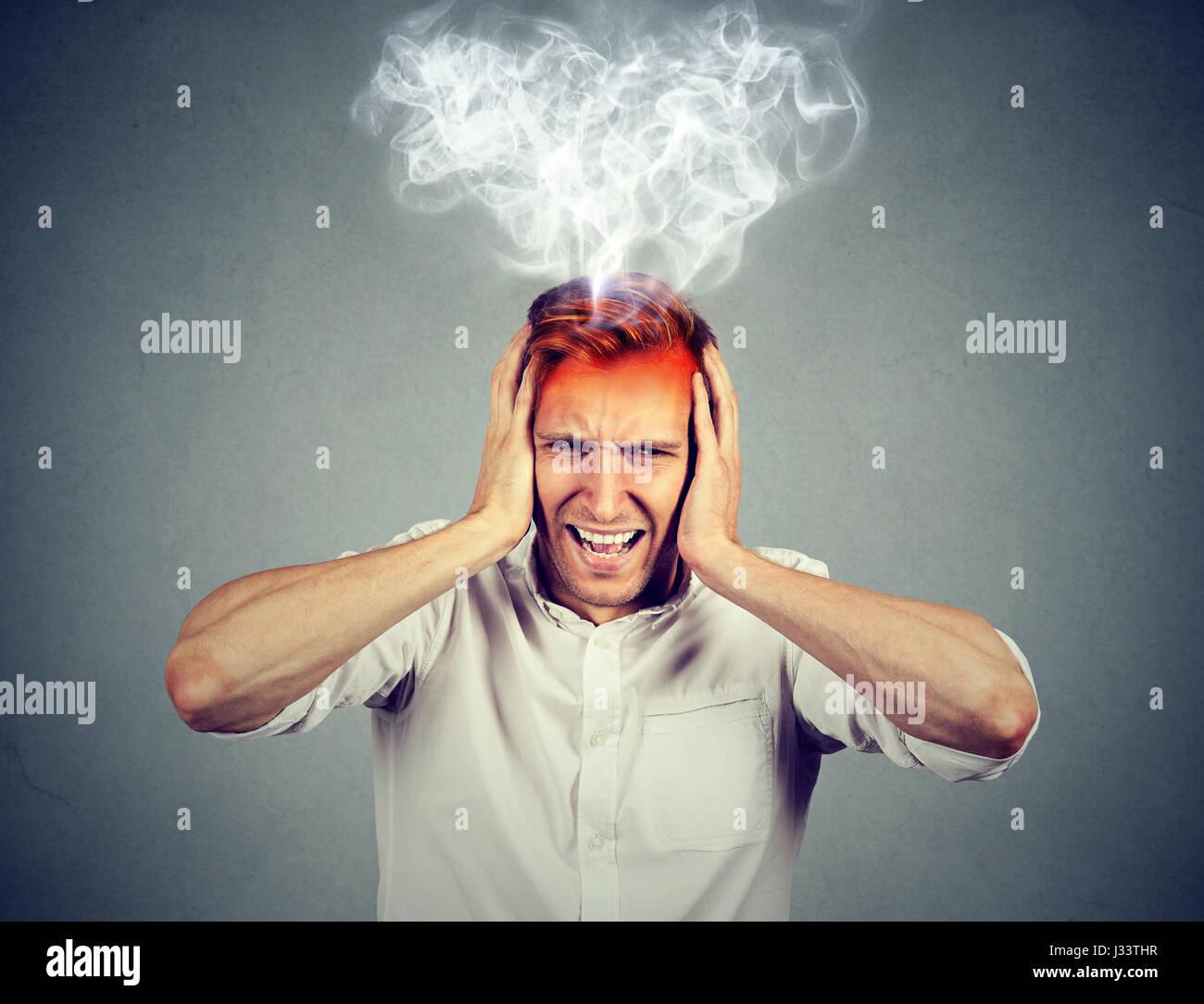 Portrait young a souligné l'homme crier frustré accablé vapeur s'échappant des chef Photo Stock