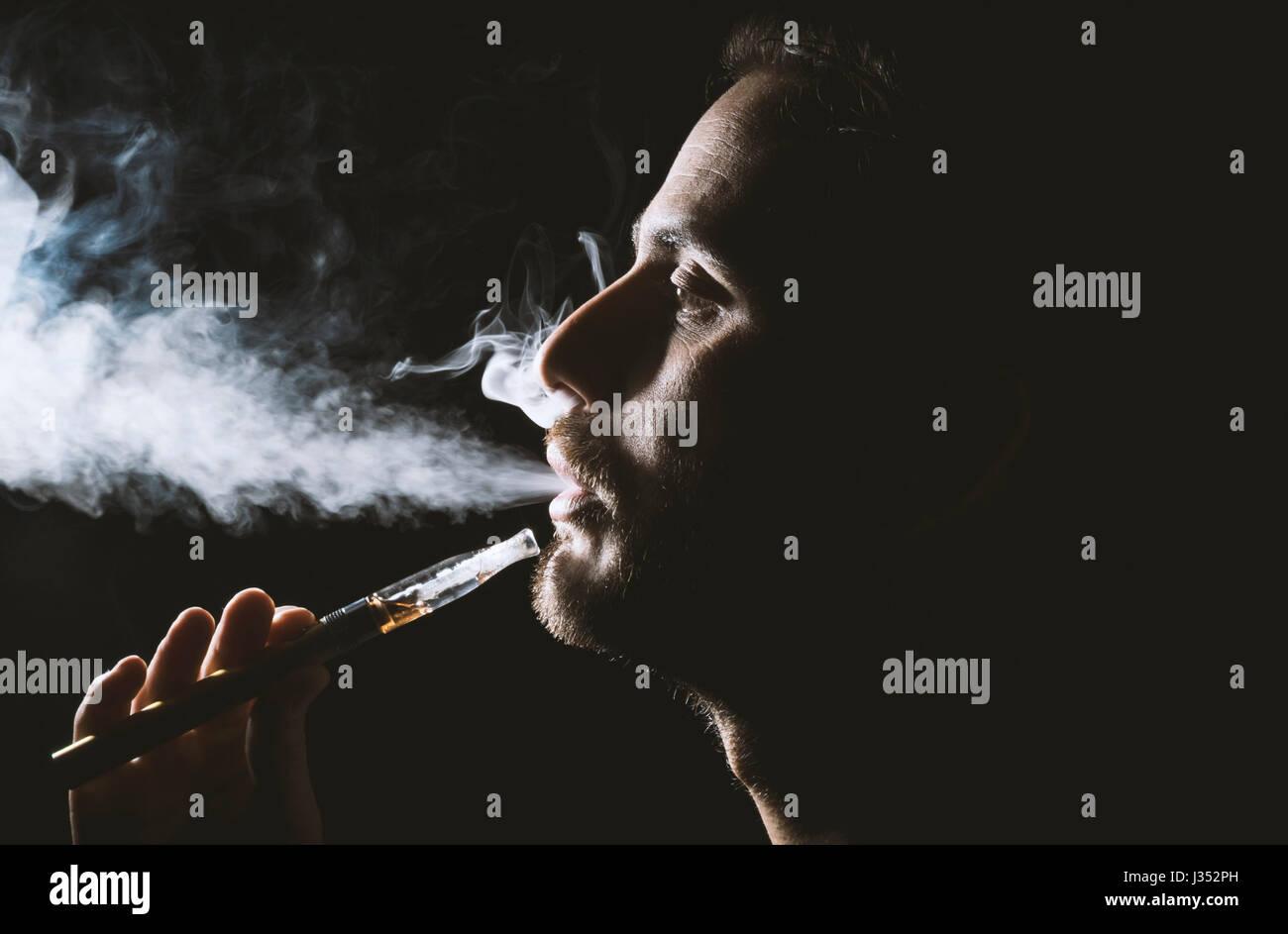 Jeune homme tenant une seine et cigarette électronique, e-CIG, cigarette electronique. Photo Stock