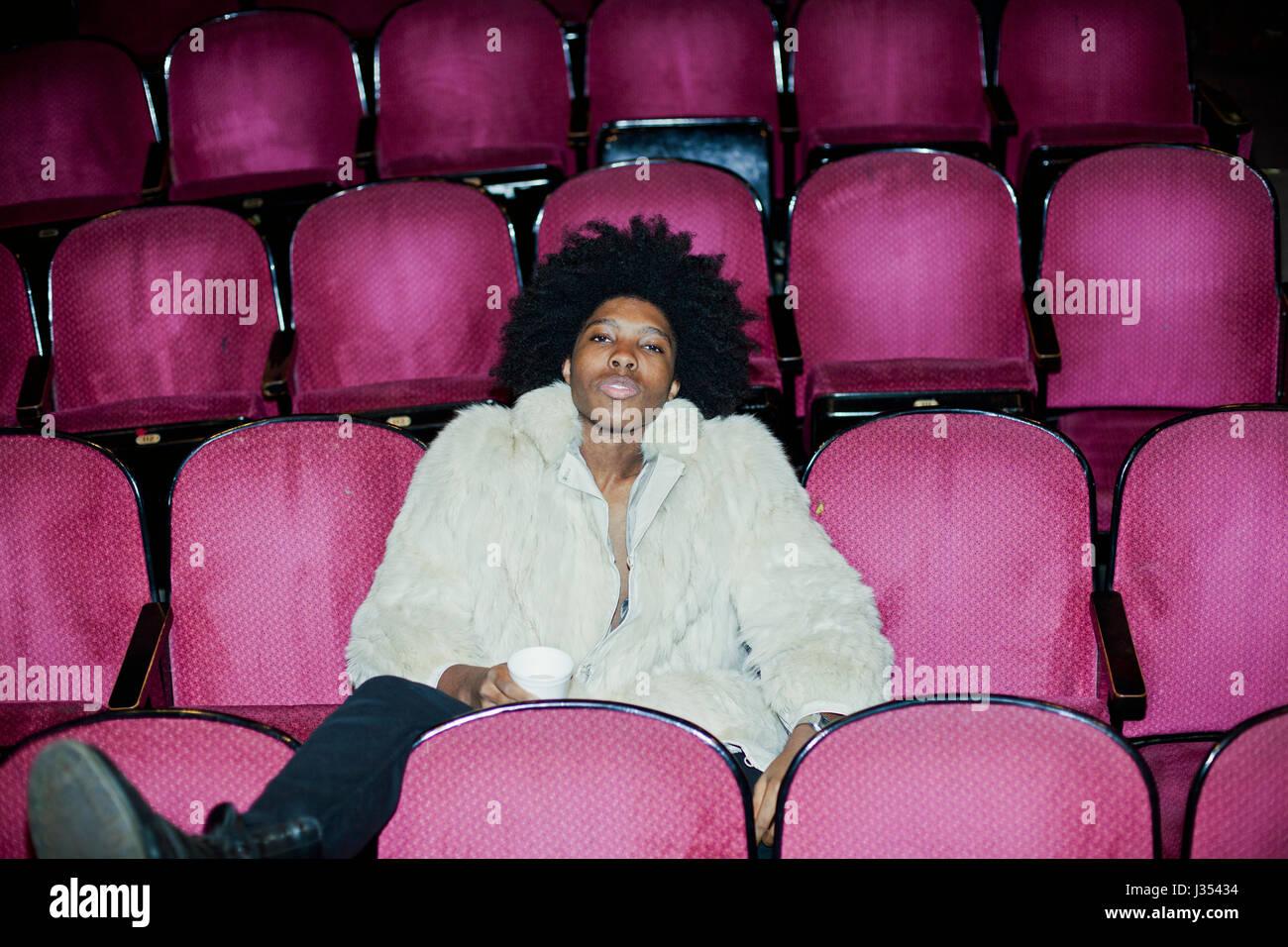 Portrait d'un jeune homme dans un manteau de fourrure dans un théâtre Photo Stock
