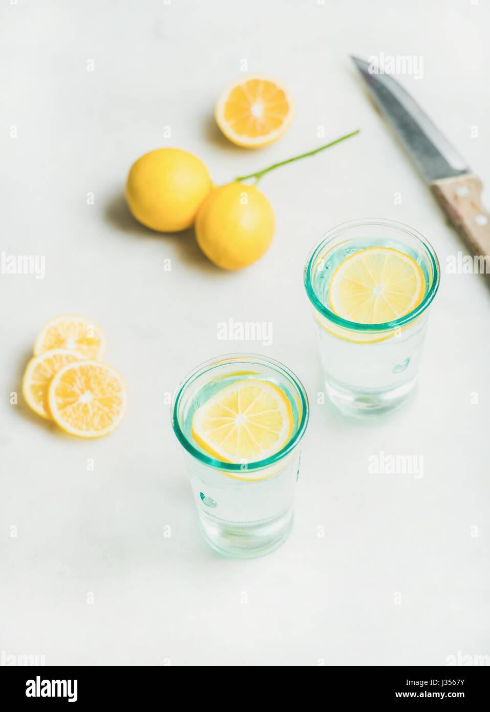 L'eau de citron detox matin dans des verres plus de lumière en arrière-plan Photo Stock