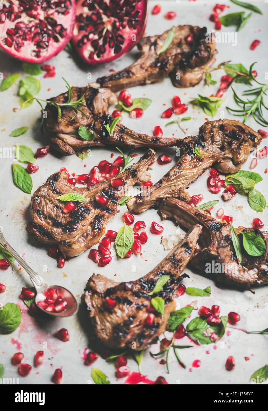 Côtes d'agneau grillées avec graines de grenade, menthe et romarin frais Photo Stock