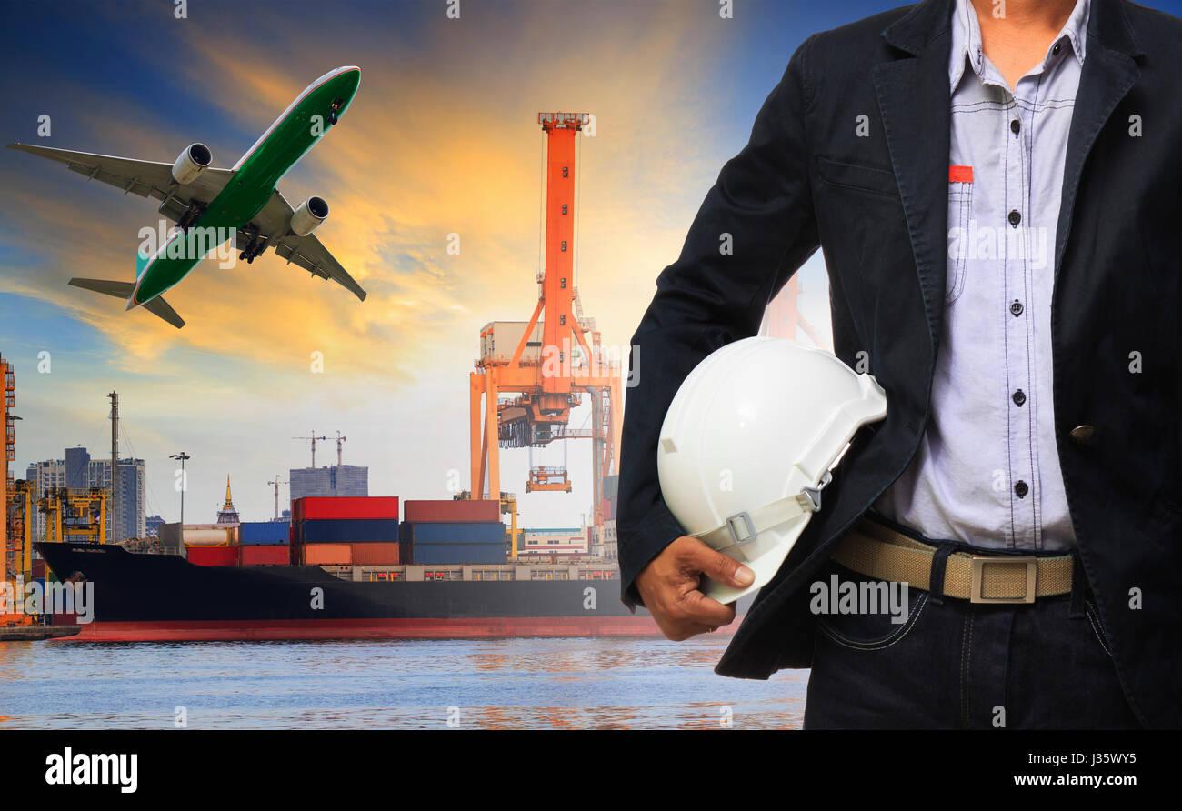 Manager man holding casque de sécurité se tenir contre le navire et récipient sur port d'expédition Photo Stock
