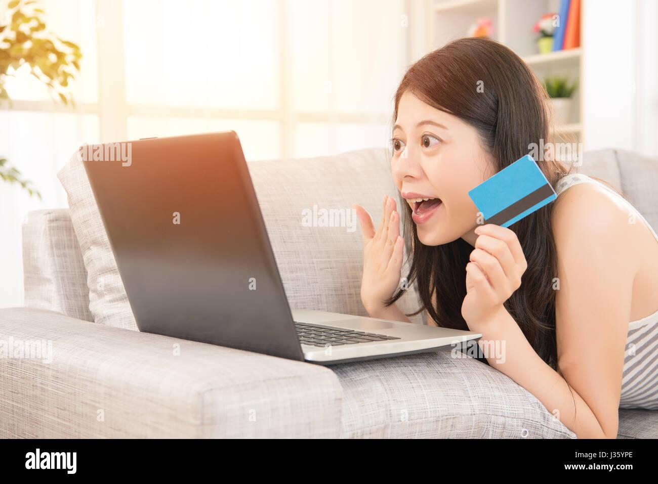 57c3ece3bf46b L'euphorie woman shopping online assis sur un canapé confortable et une  carte de crédit