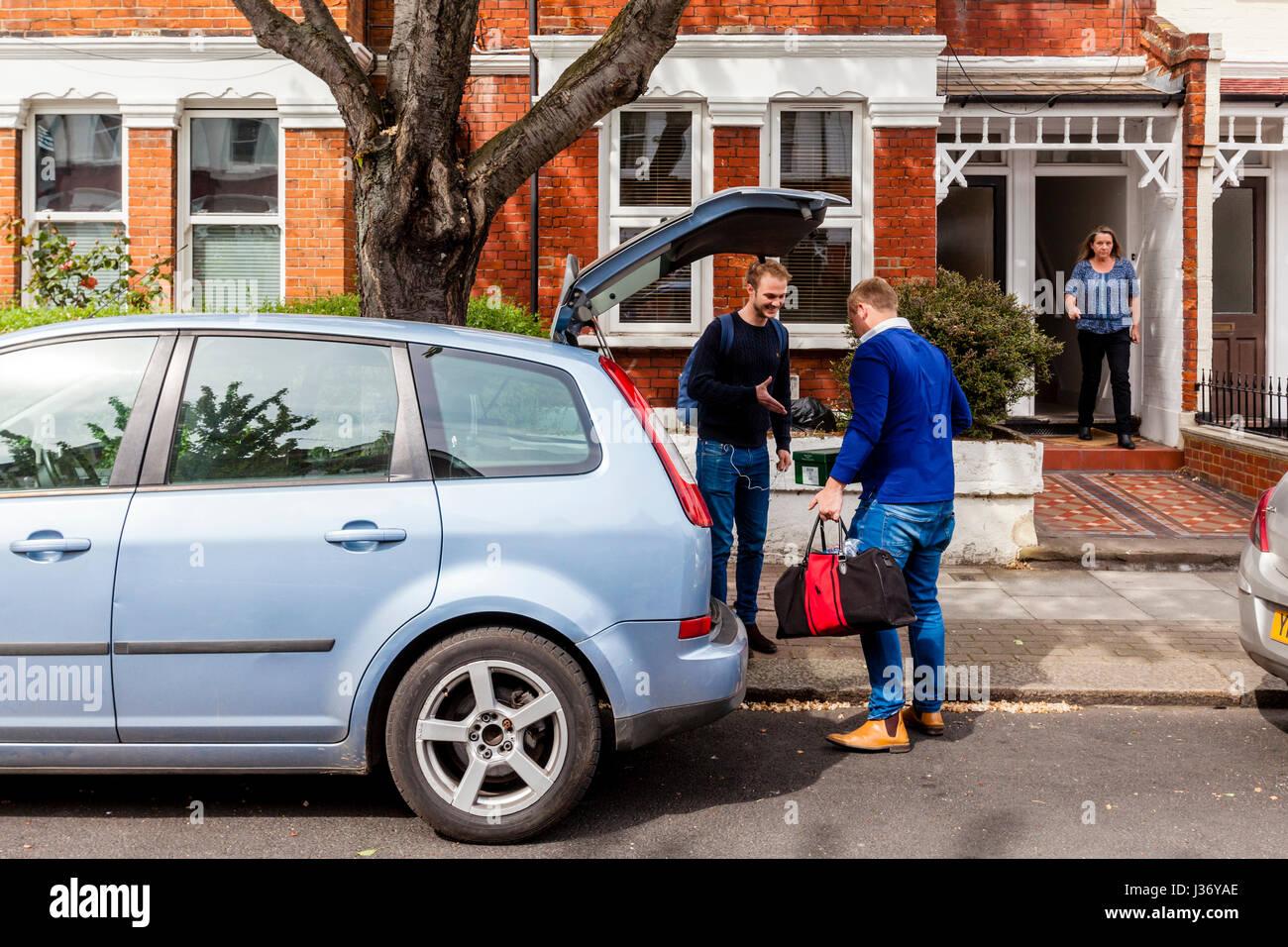 Un jeune homme se félicitant de son nouveau voisin, Londres, Angleterre Photo Stock