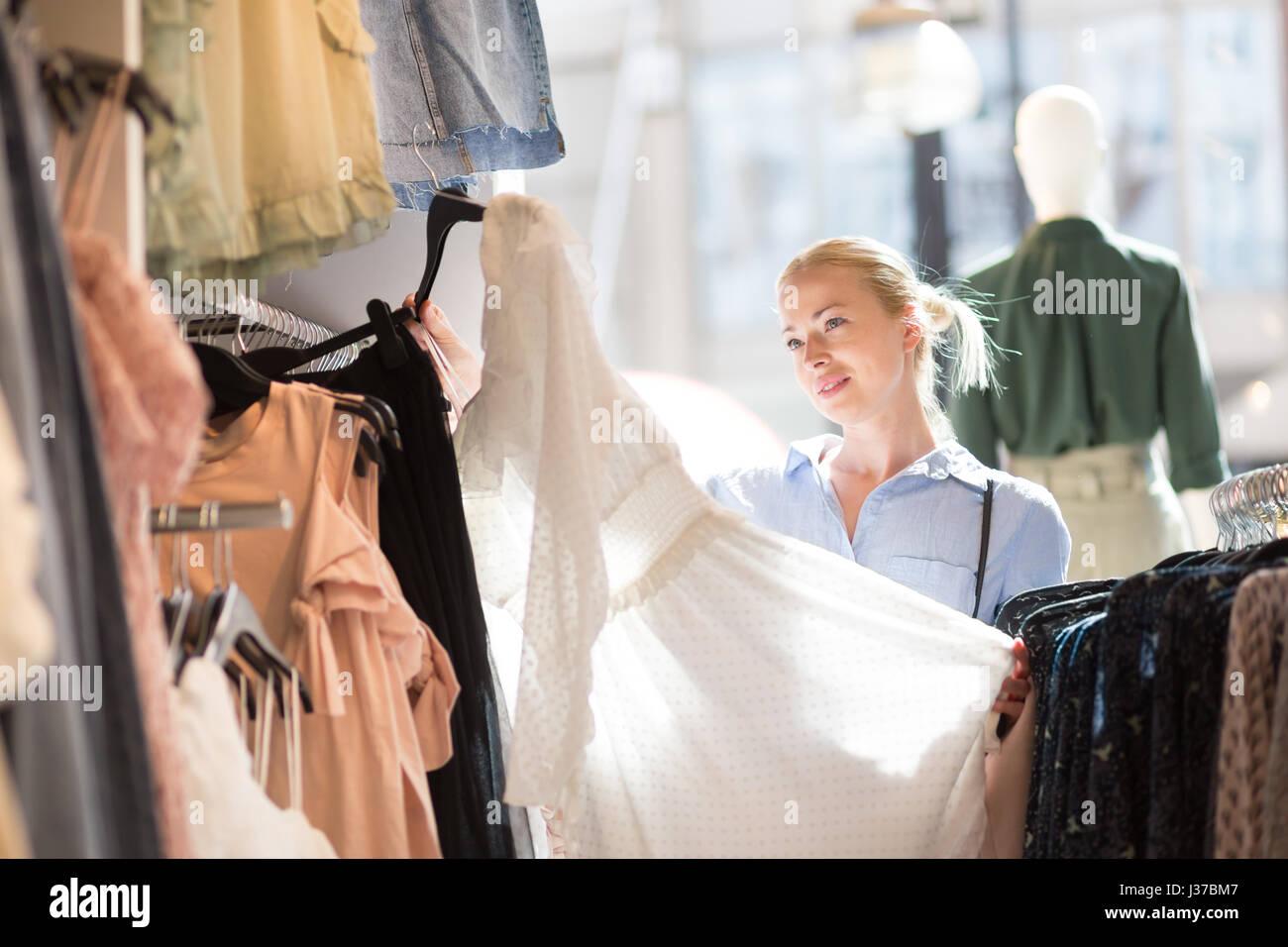 Belle femme shopping des vêtements à la mode dans une boutique de vêtements. Photo Stock