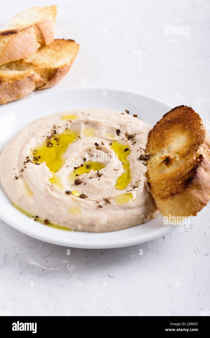 Dip de haricots blancs sur la plaque, végétalien accompagnement pate, délicieux apéritif, casse Photo Stock